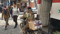 Житель Дамаска с коробкой гумпомощи из России