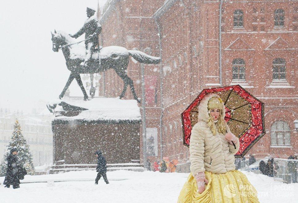 Женщина с зонтом на Манежной площади во время снегопада в Москв