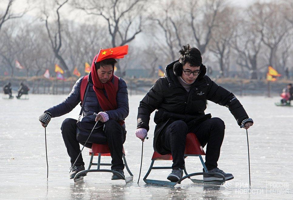 Туристы катаются на санках по льду озера Куньмин на окраине Пекина