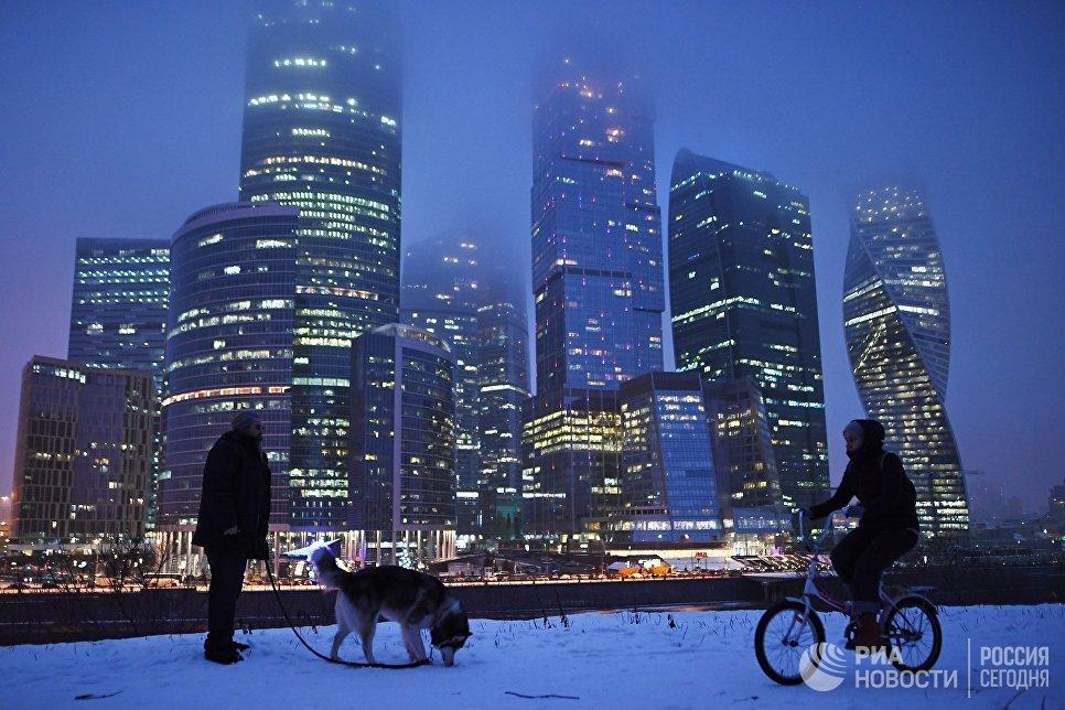 Прохожие гуляют на набережной Тараса Шевченко в Москве. На втором плане - Международный деловой центр Москва-Сити