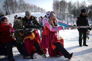 Состязание по перетягиванию каната на праздничных гуляниях, посвященных проводам Широкой Масленицы в Новосибирской области. 17 февраля 2018