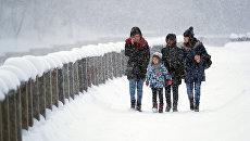 Прохожие во время снегопада на Лужнецкой набережной в Москве. архивное фото