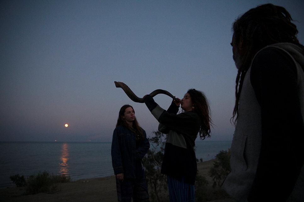 Женщина трубит в шофар на берегу Мертвого моря