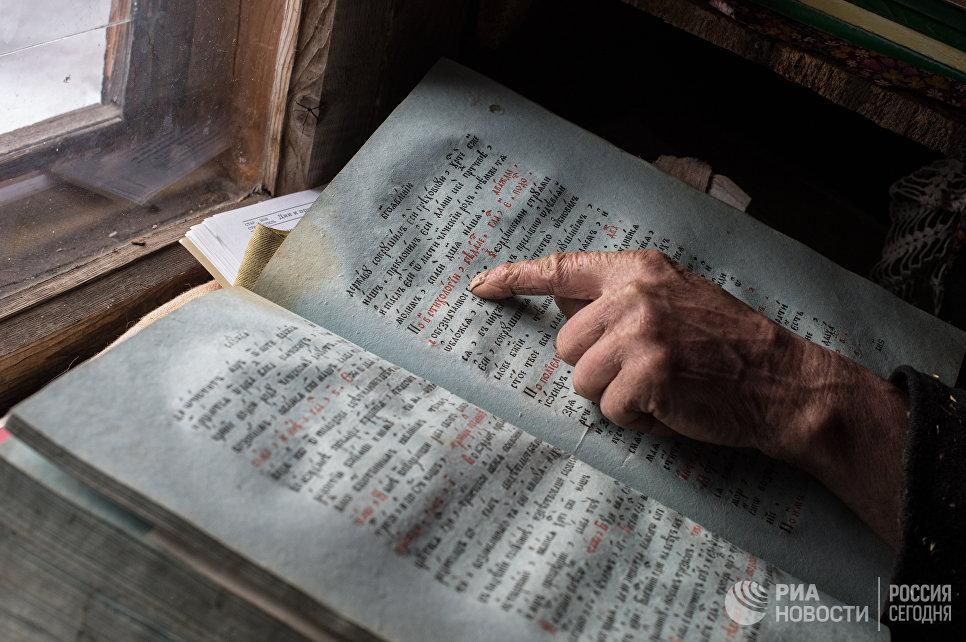 Агафья Лыкова показывает книги, оставшиеся ей от родителей.