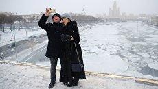Люди фотографируются на арке Парящего моста парка Зарядье в Москве. Архивное фото