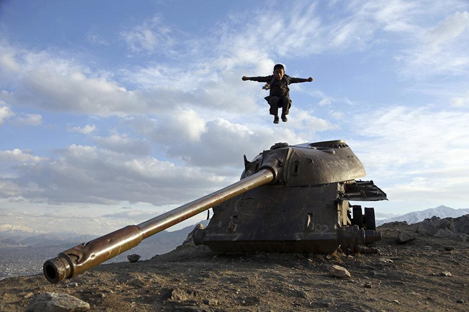 Афганский мальчик прыгает с башни советского танка на вершине холма на окраине Кабула