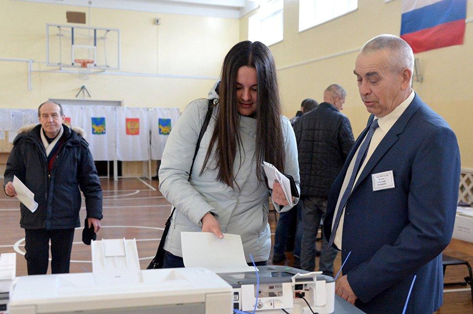 Девушка опускает бюллетень в урну на выборах президента РФ на избирательном участке во Владивостоке.