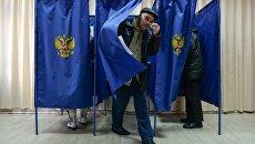Мужчина выходит из кабинки во время голосования на выборах президента Российской Федерации на избирательном участке в Новосибирске. 18 марта 2018