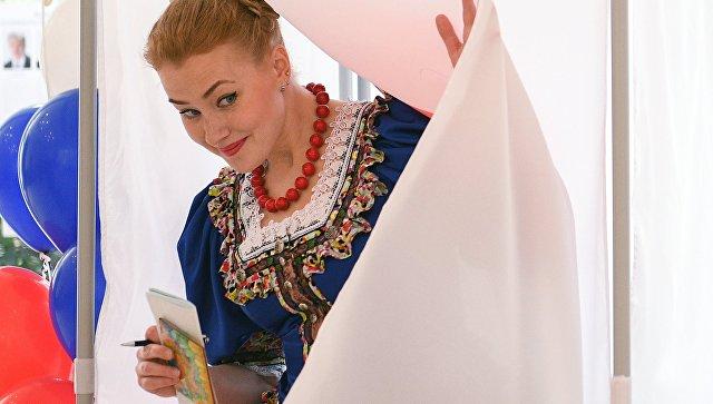 Девушка в национальном костюме выходит из кабинки во время голосования на выборах президента Российской Федерации на избирательном участке №4660 в Сочи