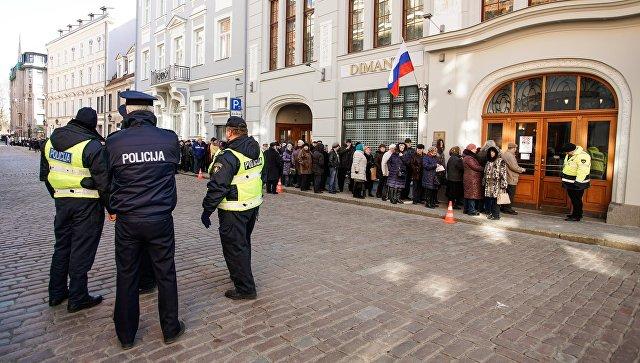 Люди стоят в очереди в российский консульский отдел в Риге, чтобы проголосовать на выборах президента РФ