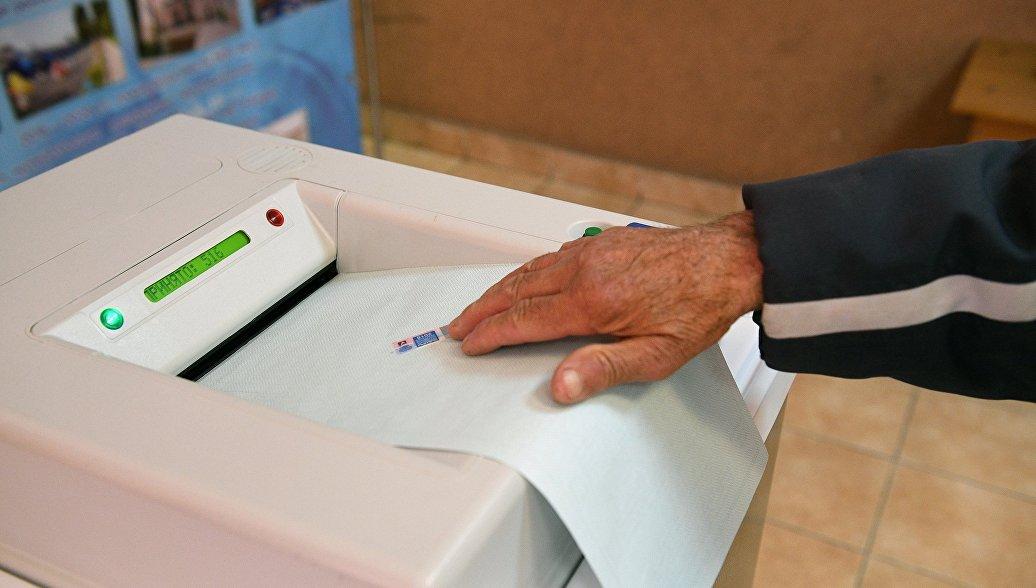 Мужчина кладет бюллетень в комплекс обработки избирательных бюллетеней (КОИБ) на избирательном участке №4660 в Сочи. Архивное фото