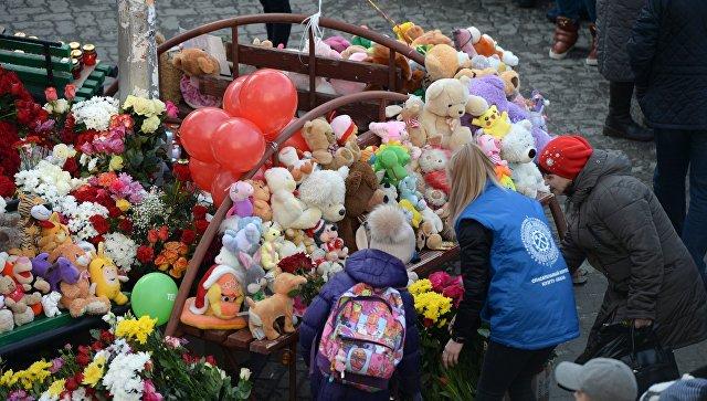 Цветы и мягкие игрушки возле здания торгового центра Зимняя вишня в Кемерово, где произошел пожар