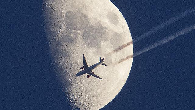 Самолет пролетает на фоне луны во Франкфурте, Германия