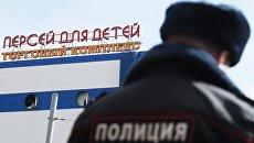 Сотрудник правоохранительных органов у детского торгового центра Персей в Москве, где произошло возгорание