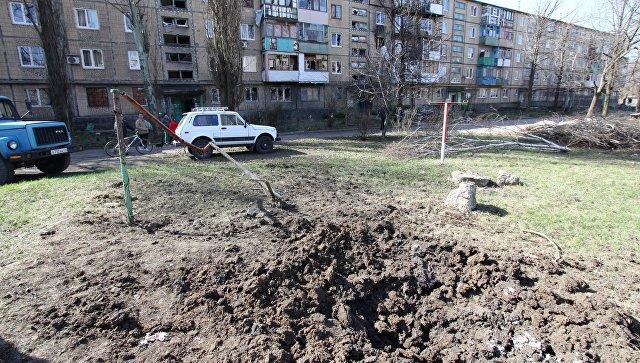 Воронка от снаряда во дворе жилого дома послеобстрела в Донецке. Архивное фото