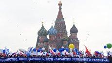 Участники первомайской демонстрации несут плакат Единство, солидарность, труд - гарантия успешного развития на Красной площади в Москве
