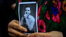 Портрет  Селахаттина Демирташа  в руках человека стоящего возле возле здания суда Бакиркой в Стамбуле. Архивное фото