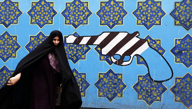 Иранская женщина проходит мимо граффити на стене бывшего посольства США в Тегеране. Архивное фото