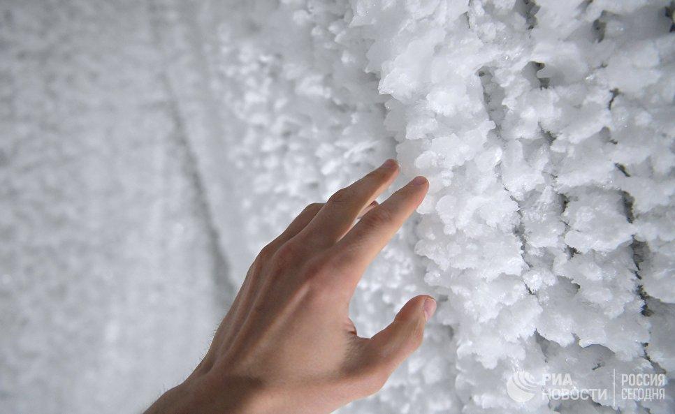 Рука посетителя в павильоне Ледяная пещера в природно-ландшафтном парке Зарядье в Москве