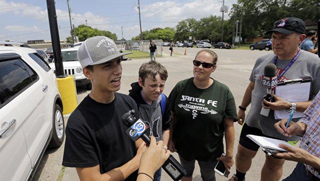 Ученик школы Санта-Фе Логан Робертс беседует с журналистами возле тренажерного зала, где студенты и родители ожидают после в стрельбы в  школе Санта-Фе. 18 мая 2018