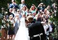 Британский принц Гарри и его жена Меган Маркл выходят из церкви Святого Георгия в Виндзоре, Англия. 19 мая 2018 года
