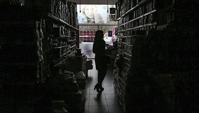 Покупательница в обесточенном торговом зале одного из магазинов в Симферополе. Архивное фото