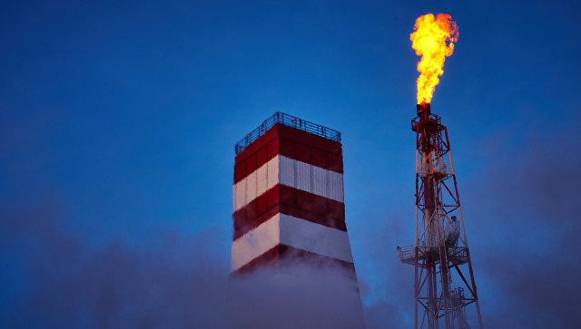 Буровая вышка и газовый факел морской нефтеперерабатывающей платформы