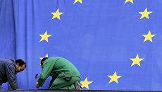 Рабочие прикрепляют флаг Европейского союза возле штаб-квартиры ЕС в Брюсселе. Архивное фото