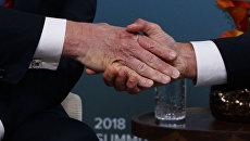 Рукопожатие президентов США и Франции Дональда Трампа и Эммануэля Макрона на саммите G7. 8 июня 2018