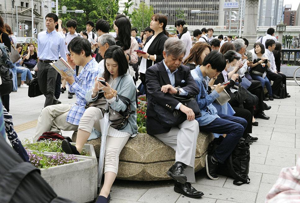 Люди сидят возле станции Йодоябаши после землетрясения