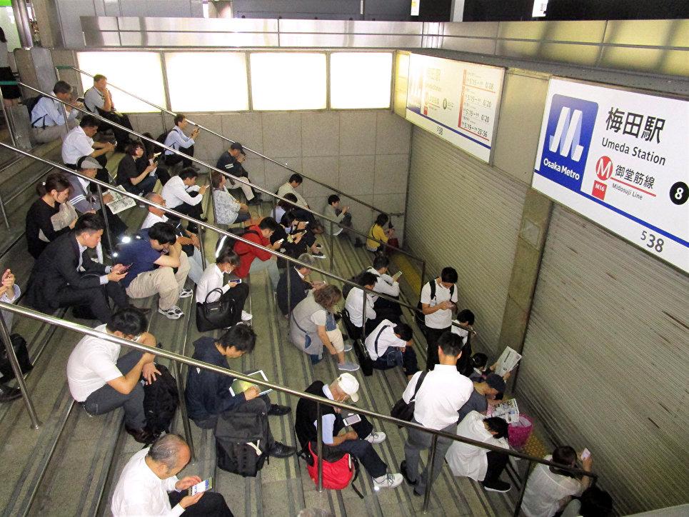 Люди сидят возле станции после землетрясения в Осаке