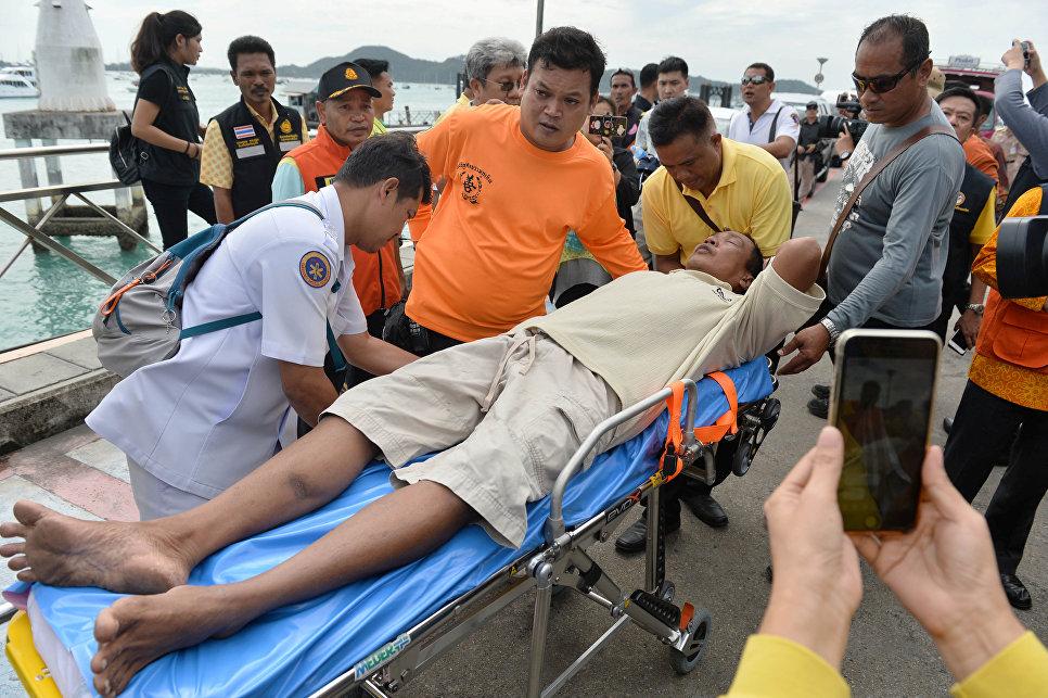 Спасатели оказывают помощь пассажиру перевернувшейся туристической лодки на Пхукете, Таиланд. 6 июля 2018
