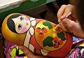 Сотрудница производственного художественного объединения Хохломская роспись расписывает матрешку в цехе предприятия