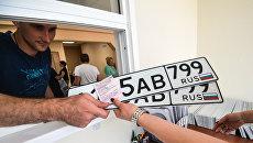 Выдача автовладельцу номерных знаков в одном из отделов регистрации транспортных средств ГИБДД по Москве. Архивное фото
