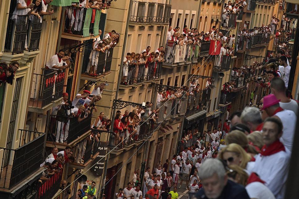 Зрители наблюдают за участниками фестиваля Сан-Фермин в Памплоне, Испания. 9 июля 2018 года