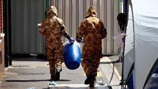 Сотрудники британских спецслужб в защитных костюмах у жилого дома в Солсбери в связи с расследованием отравления людей в Эймсбери. 6 июля 2018