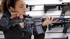 Девушка с автоматической винтовкой в магазине по продаже оружия в США. Архивное фото