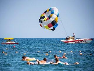 Отдыхающие купаются и катаются на парашюте