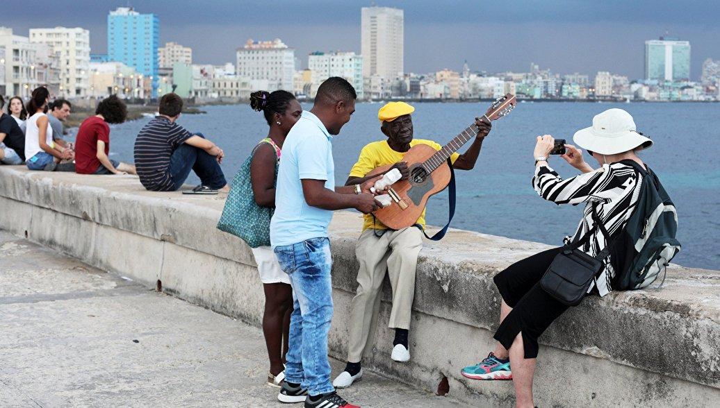 Кубинцы и туристы отдыхают на набережной Малекон в Гаване