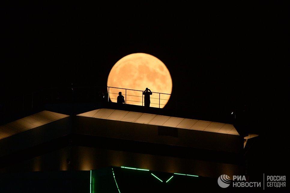 Луна во время затмения на фоне здания высотного комплекса Грозный сити в Грозном