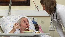 Пациент Первого московского хосписа разговаривает с врачом во время еды