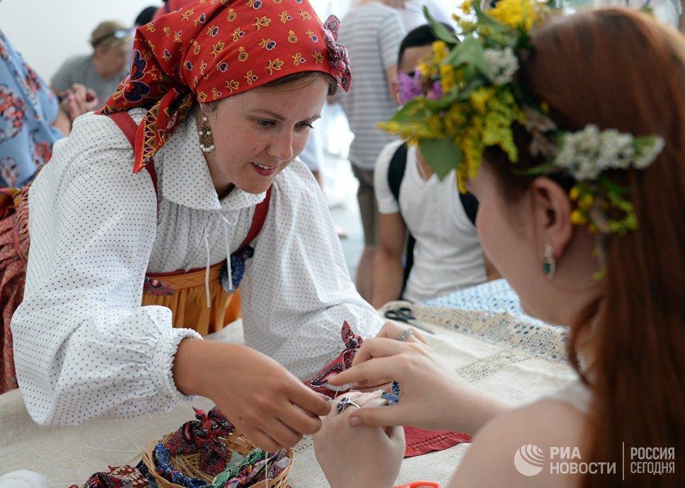 Посетители во время мастер-класса по изготовлению кукол на фестивале Многонациональная Россия в Москве
