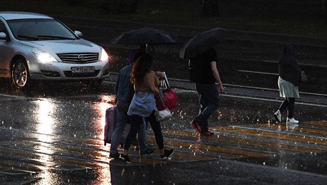 Прохожие переходят дорогу во время дождя в Москве. Архивное фото