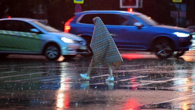 Прохожий переходит дорогу во время дождя в Москве. архивное фото