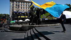 Мужчина с украинским флагом у памятника основателям Киева на площади Независимости