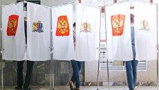 Избиратели в кабинках в единый день голосования на избирательном участке