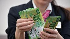 Сотрудница банка проводит денежные операции с новыми купюрами номиналом 200 и 2000 рублей в банке ВТБ в Москве. Архивное фото