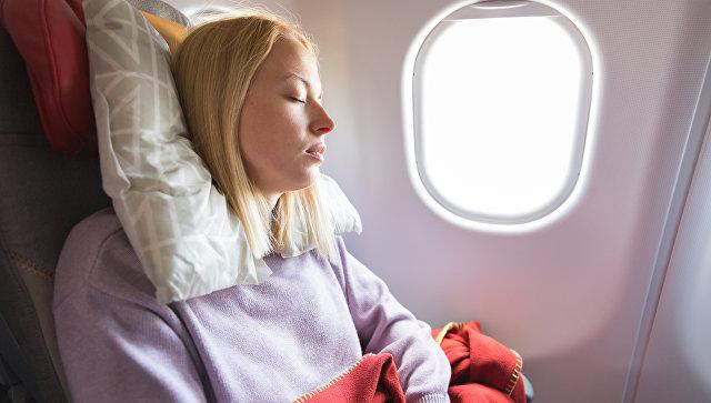 Девушка спит в салоне самолета