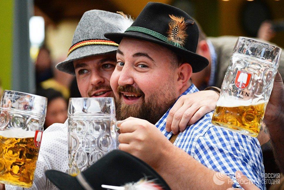 Посетители с бокалами пива на открытии традиционного пивного фестиваля Октоберфест в Мюнхене