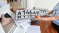 Выдача автомобильных номеров в отделе регистрации ГИБДД. Архивное фото